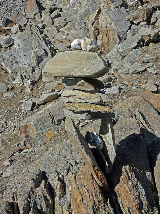 Foto: vince 51 / Wander Tour / Kreuzspitze - auf den höchsten Wanderberg der Ostalpen (3457m) / Kunstvolles Steinmännchen. Am Weg zum Kreuzkogel wird ein Gelände mit einer Vielzahl von mehr oder weniger kunstvoll aufgebauten Steinmännchen passiert. Auf diesem Wegabschnitt ist besonders auf Steigspuren und Farbmarkierungen zu achten um nicht von den teils weit von der richtigen Route entfernten Männchen in die Irre geleitet zu werden. Allerdings besteht aufgrund der Geländebeschaffenheit keine Gefahr für den Wanderer! ( relativ flaches Felsgelände ohne Absturzgefahr) / 17.07.2009 22:25:31