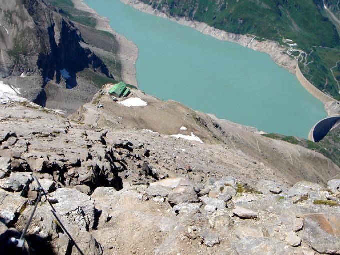Foto: Manfred Karl / Wander Tour / Vom Mooserboden auf das Große Wiesbachhorn (3564 m) / Tiefblick vom Unteren Fochezkopf zum Heinrich-Schwaiger-Haus und dem Stausee Mooserboden. / 26.04.2007 07:03:42