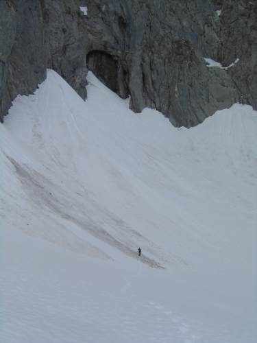 Foto: Christian Suschegg / Schneeschuh Tour / Sagenumwobenes Grimmingtor / Das Grimmingtor kann man zwar auch aus dem Tal gut erkennen.  Seine wahren Ausmaße sind aber nicht erahnbar.  Im Größenvergleich: Ein winziges Menschlein vor dem ca. 50 Meter hohen und 15 Meter breiten