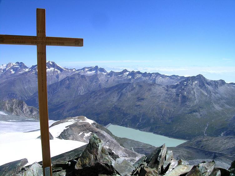 Foto: Andreas Koller / Wander Tour / Im Banne der Walliser Eisriesen auf das Fluchthorn (3791 m) / Gipfelkreuz am Fluchthorn mit Stausee Mattmark und der Weissmiesgruppe / 10.08.2007 21:37:16